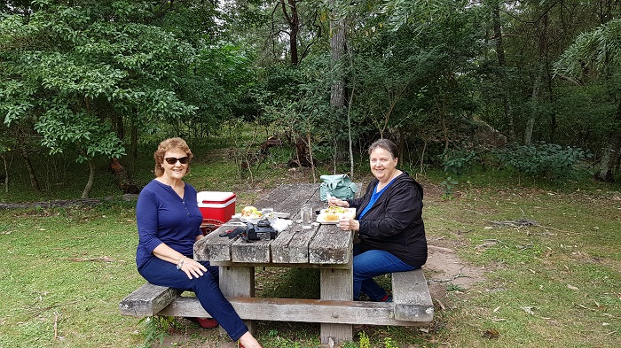 Two happy passengers enjoying a picnic lunch at Bangalee Reserve during a Shoalhaven River Cruise Picnic Cruise