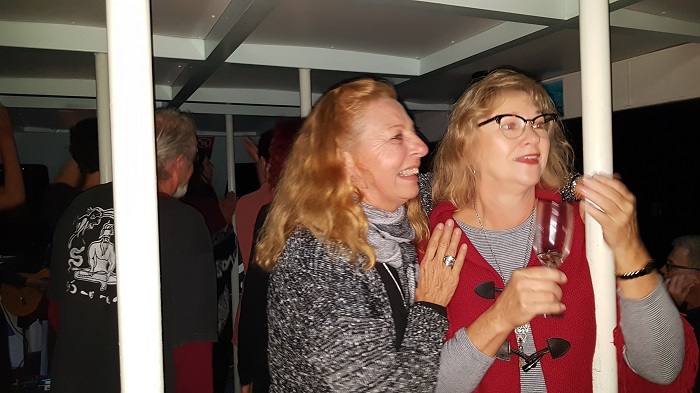 Two passengers enjoying some dancing and singing during the Groove Cruise onboard with Shoalhaven River Cruise